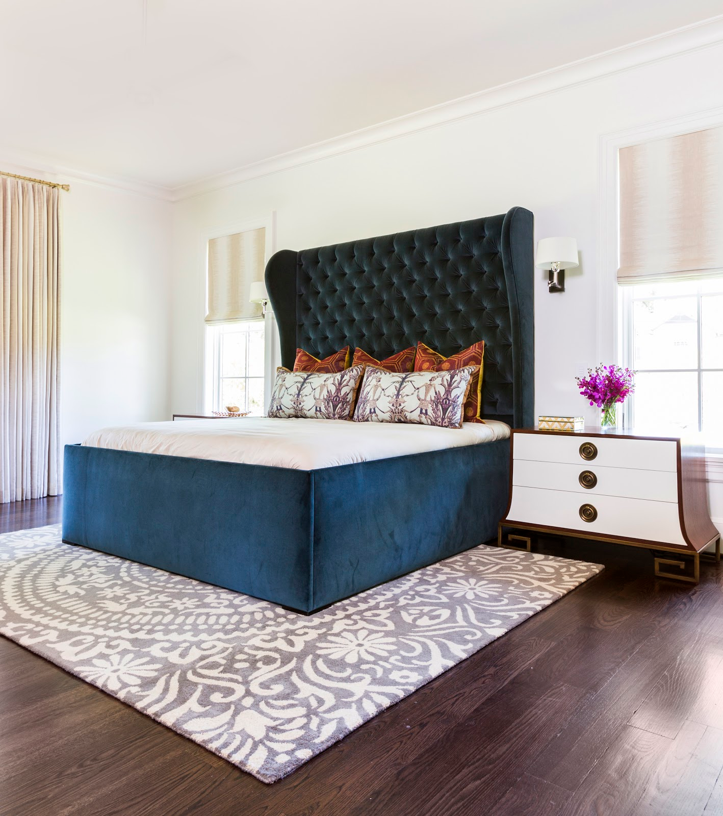 Blue velvet tufted headboard with organic neutral rug in master bedroom - laura u interior design