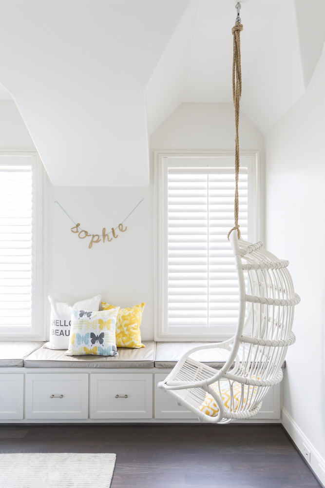 Hanging woven chair in modern kids bedroom with lots of storage - Laura U Interior Design