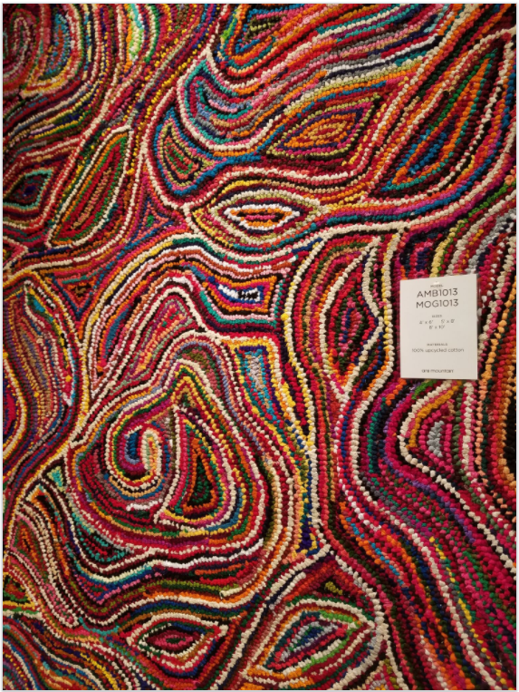 Tigres rug which has a kaleidoscopic pattern full of bold pinks, reds, blues, yellows from Las Vegas Market