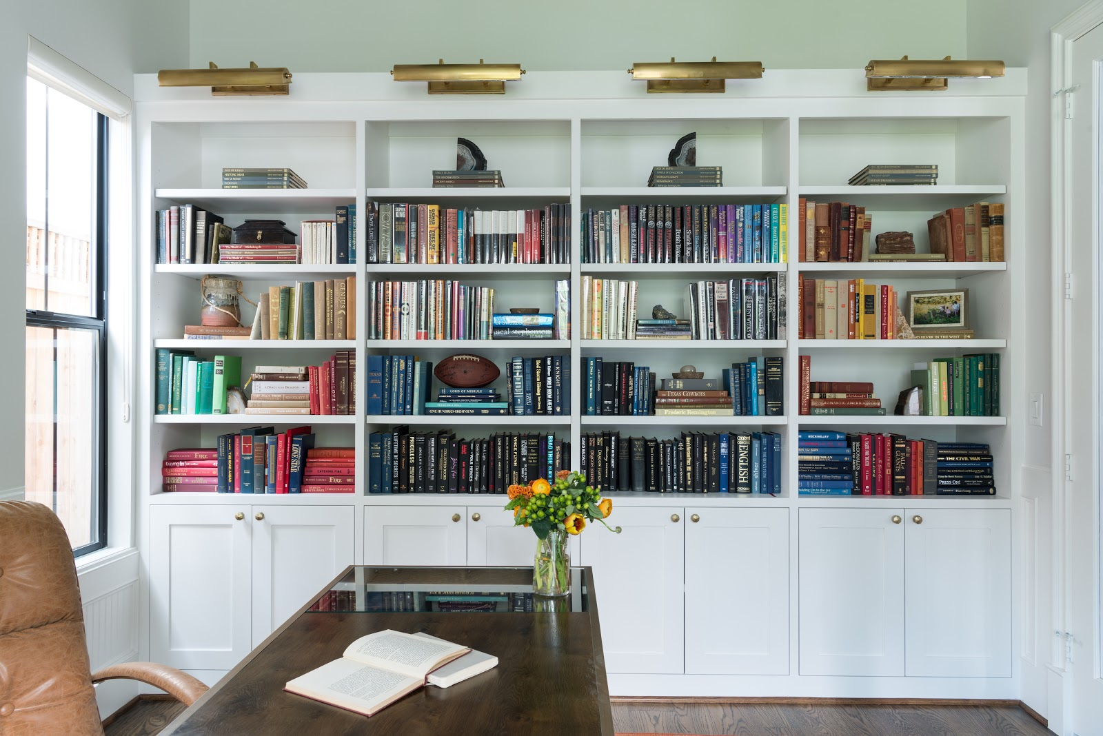 Rare book collection displayed in mid-century inspired study - Laura U Interior Design
