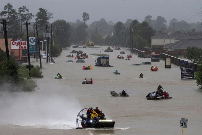 Flood affected residents are seen on boats on a flooded road in Houston, Texas, US. Photo: Reuters