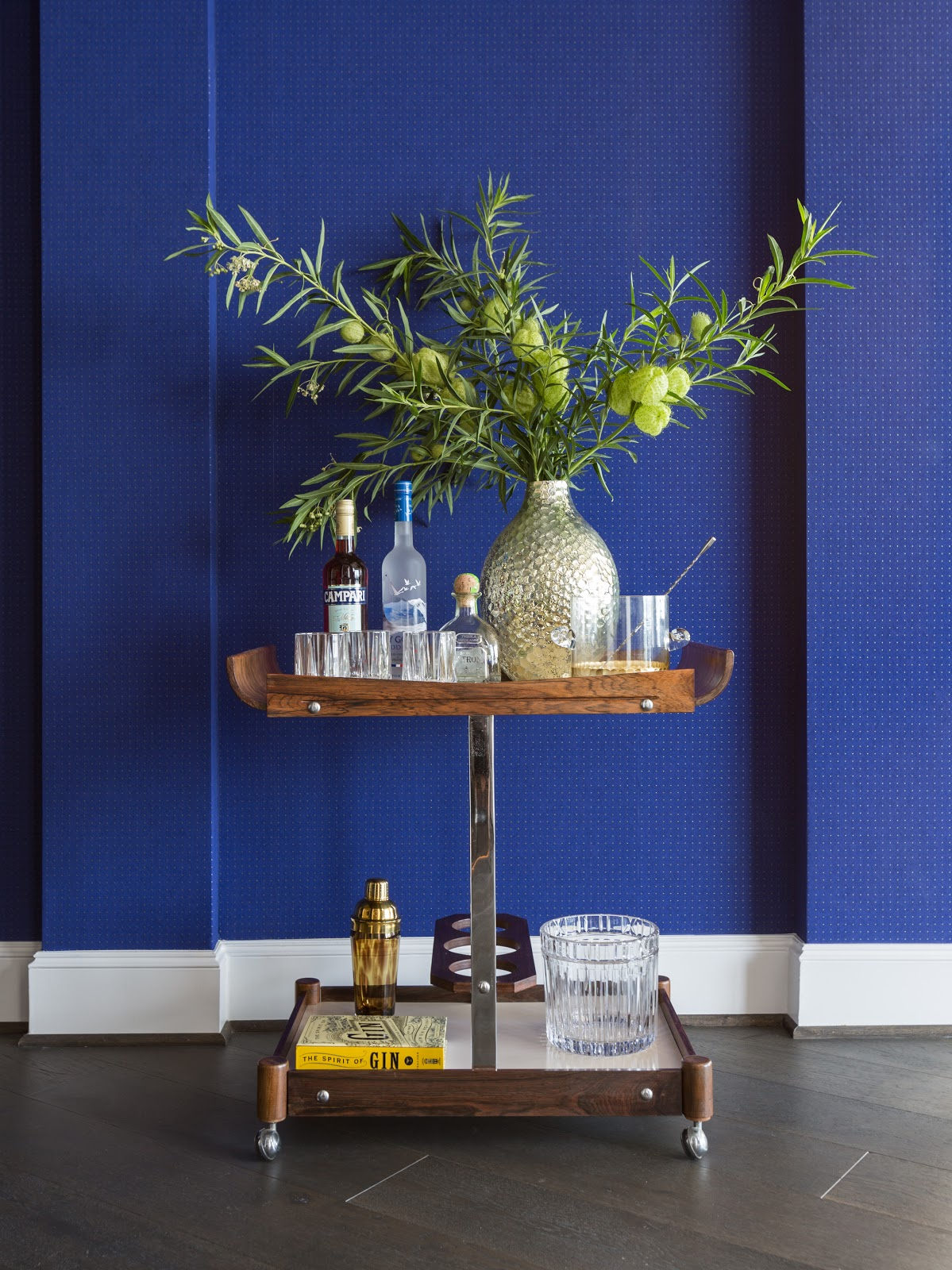 Cobalt blue bar cart with vintage spirits and barware - Laura U Interior Design
