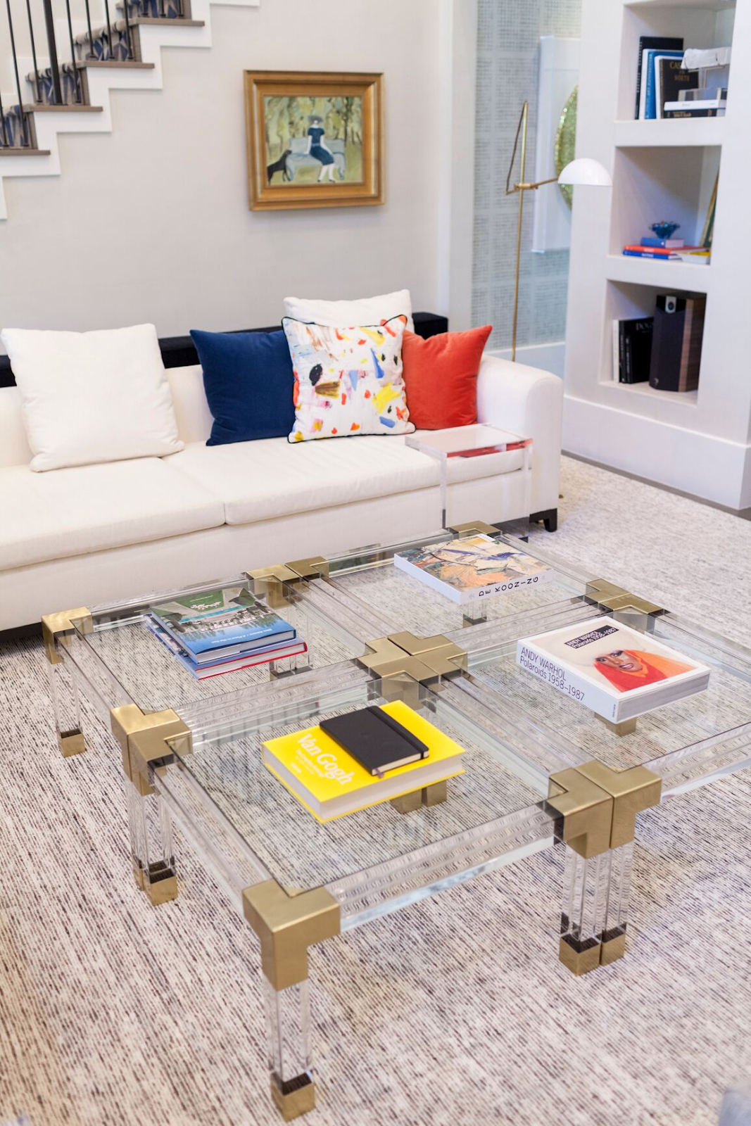 Gold and clear acrylic coffee tables with stacks of books by Laura U Interior Design