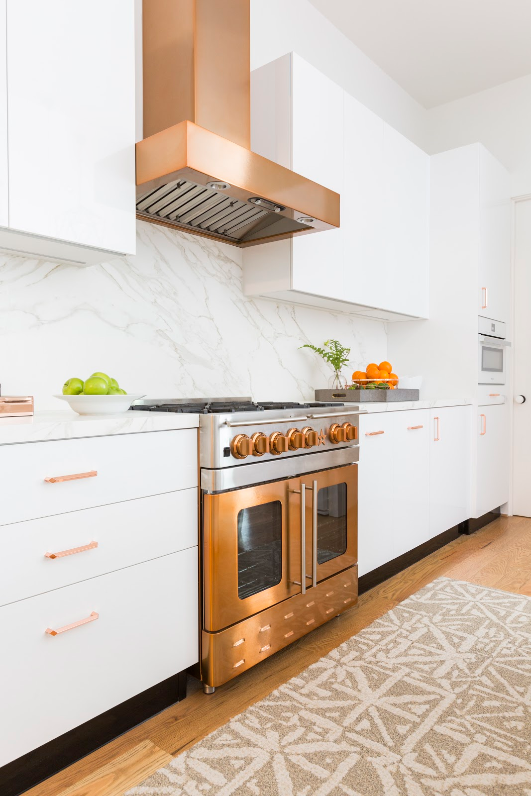 Gorgeous copper oven and vent hood with marble backsplash - Laura U Interior Design