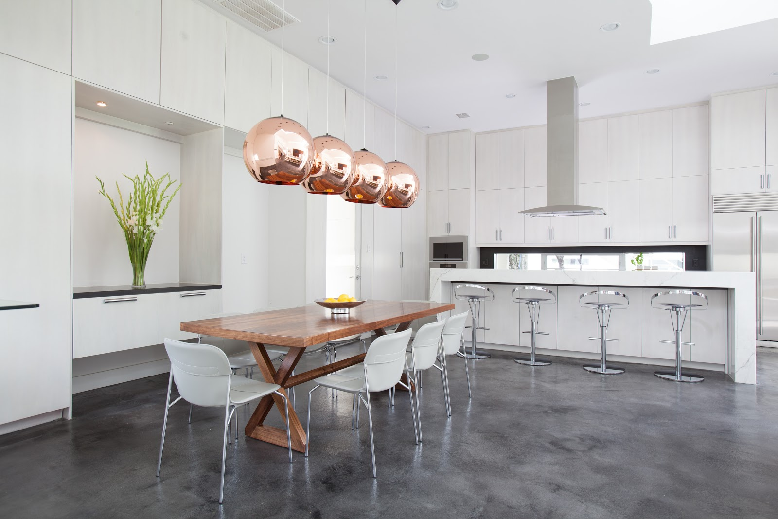 Minimalist bright white kitchen with copper lighting, mixed metals and concrete floors - Laura U Interior Design