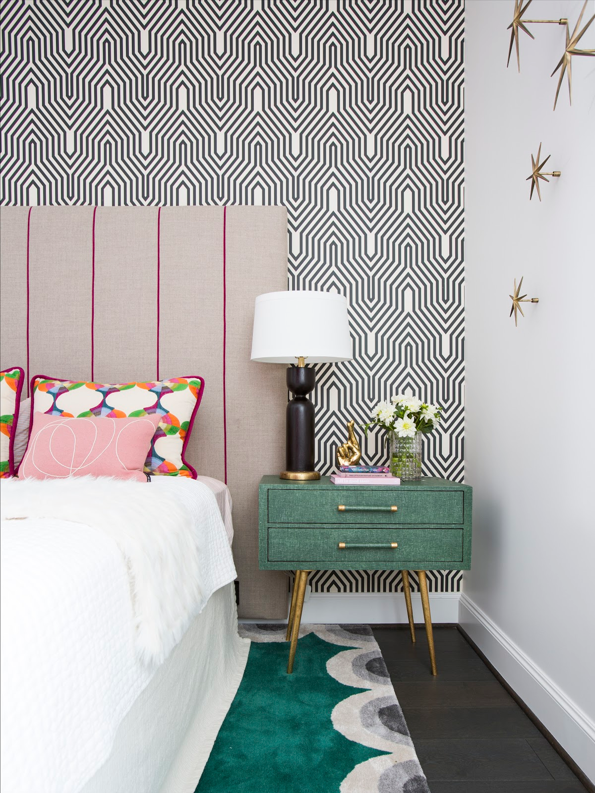 Geometric wallpaper covering as backdrop for custom pink stripe headboard in colorful guest bedroom - Laura U Interior Design