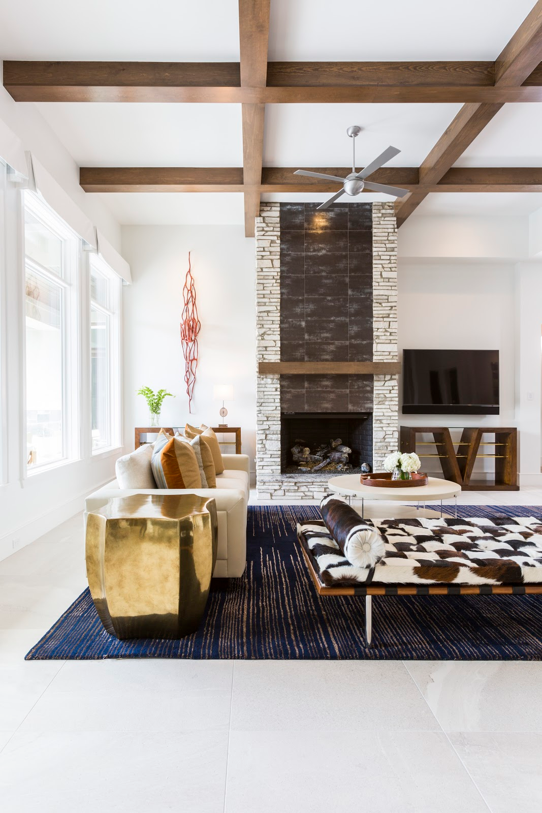 Natural brick and wooden beam bright white living room with gold and cowhide accents - Laura U Interior Design