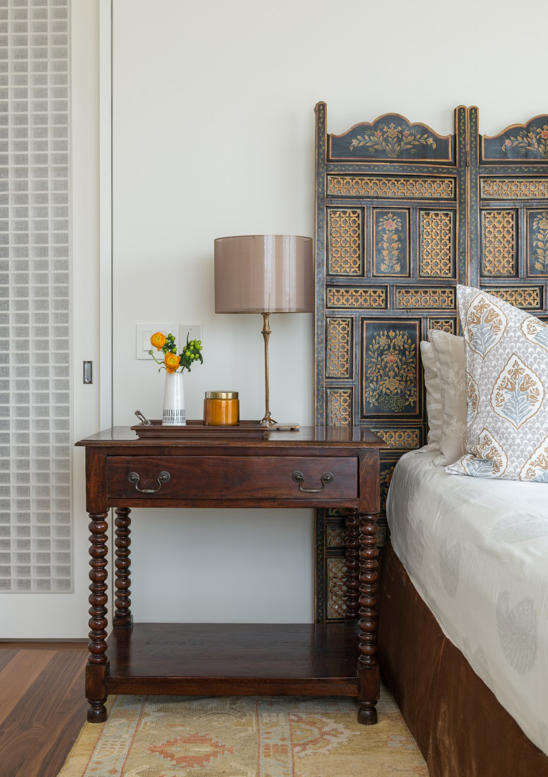 collected high-rise indo-asian inspired bedroom with wooden screen headboard and antique spindle leg nightstand - laura u interior design