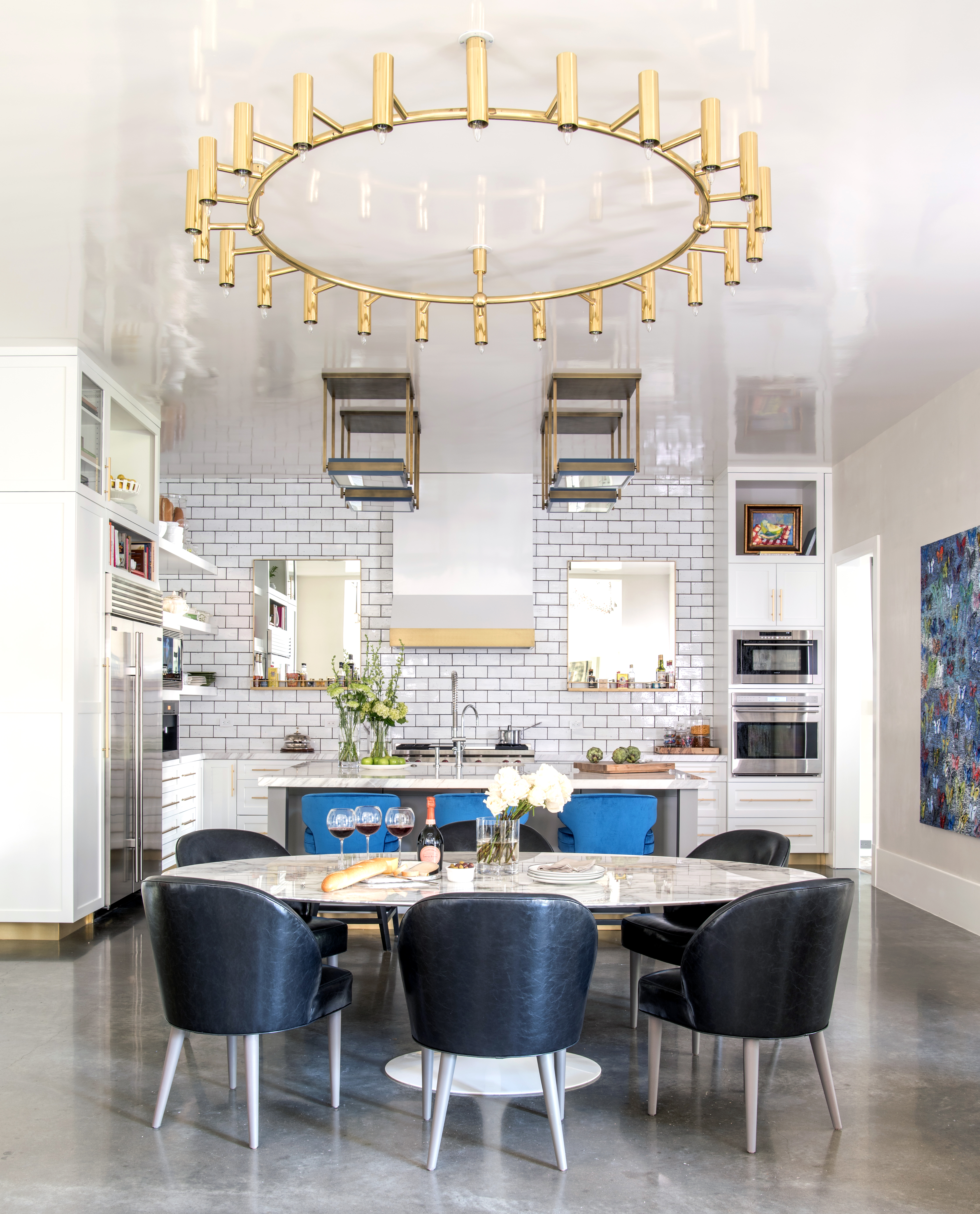 Dramatic white and gold open kitchen with large metallic accents light fixture - Laura U Interior Design