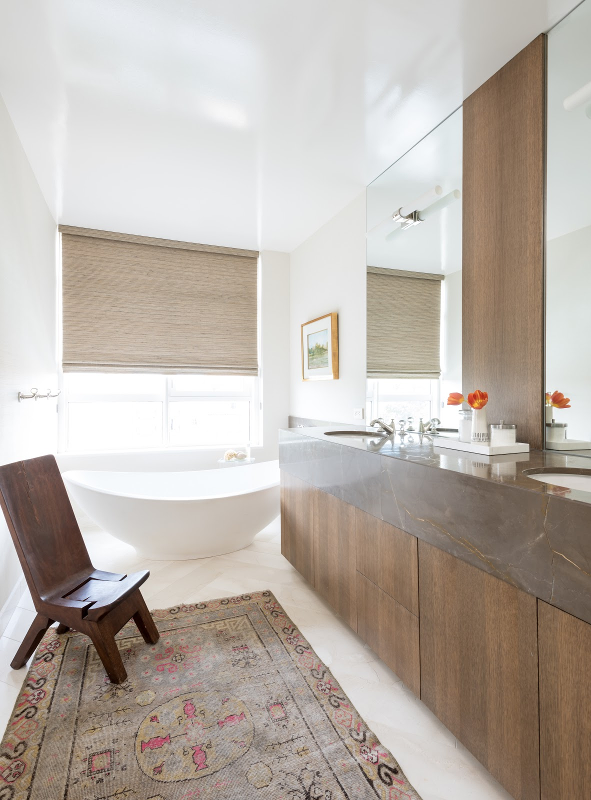 collected high-rise minimalist bathroom with wood cabinetry and freestanding tub - laura u interior design