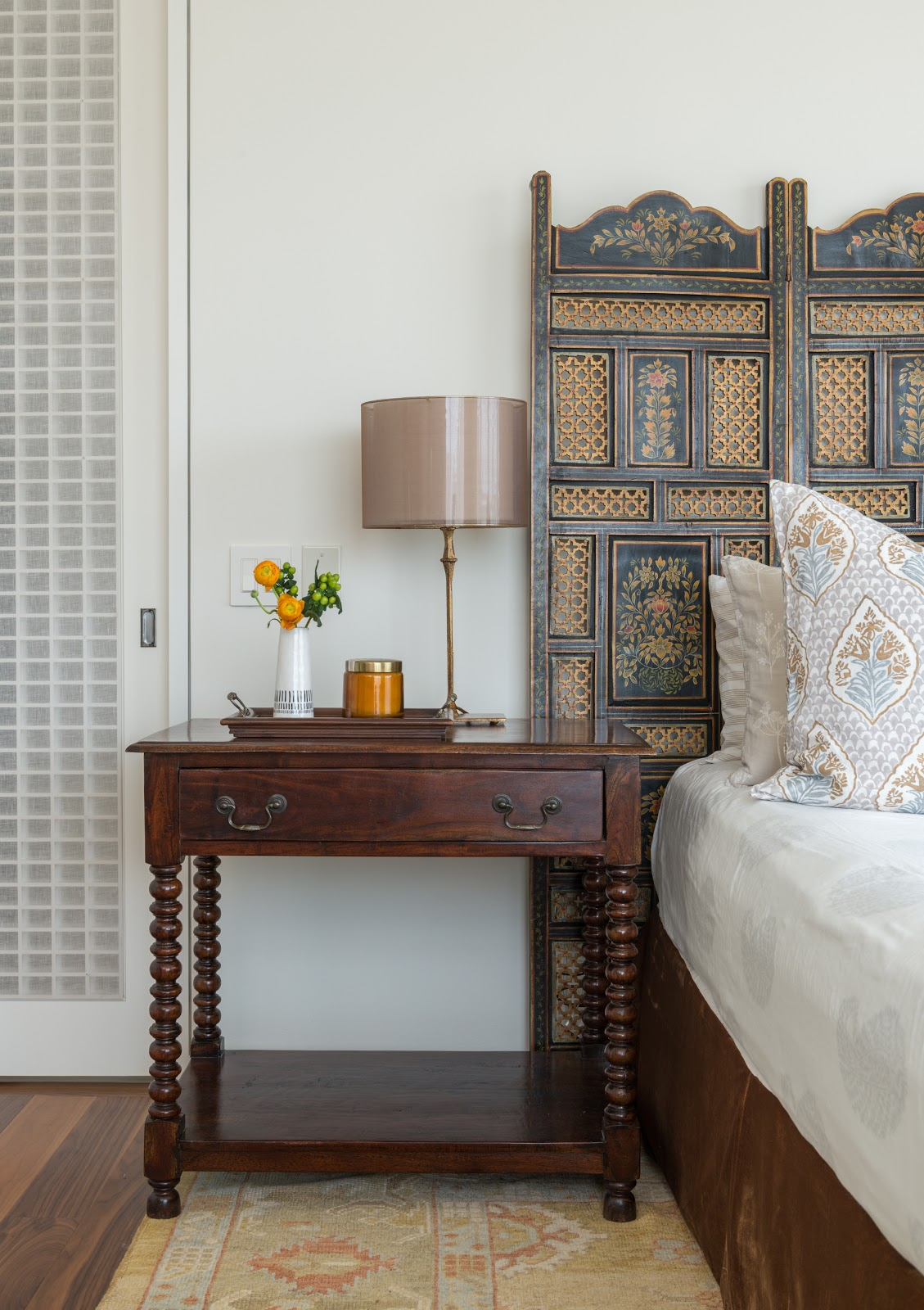 Ornate antique headboard with traditional spindle leg side table in guest bedroom - Laura U Interior Design