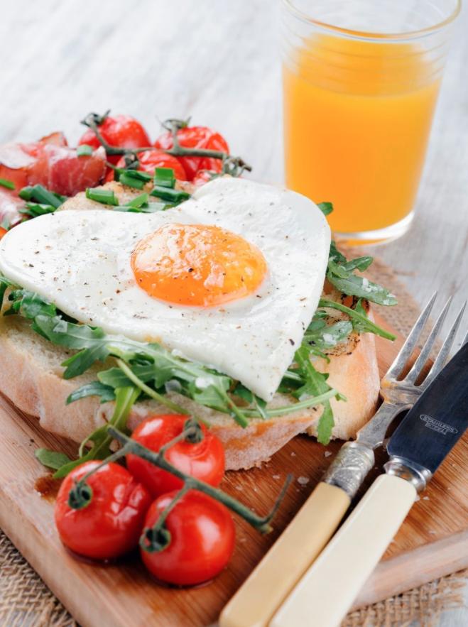 Heart shaped egg on toast with orange juice