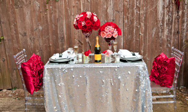 Diner table set up in backyard using pink and white colors with wine and flowers for decorations
