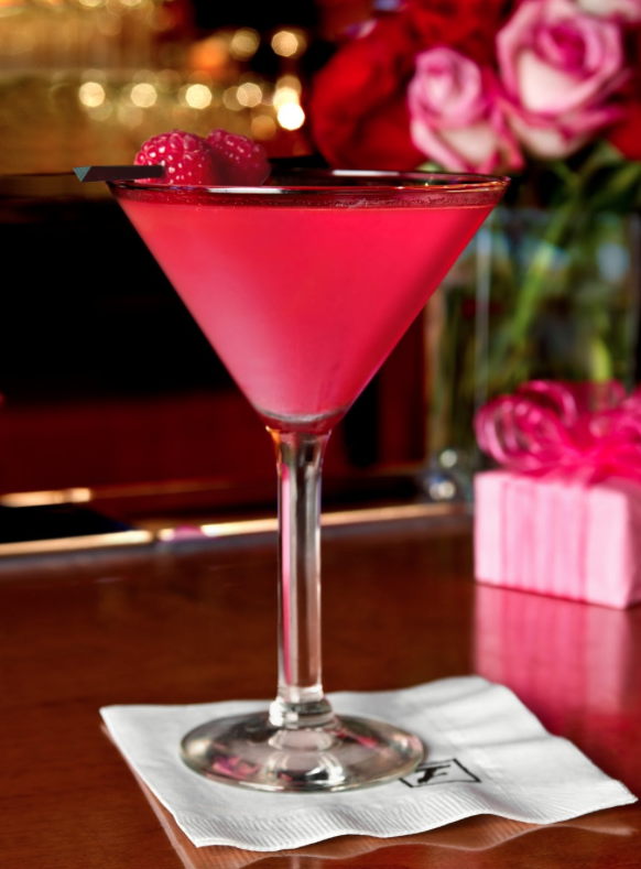 Pink cocktail with raspberries as a garnish, served in a martini glass